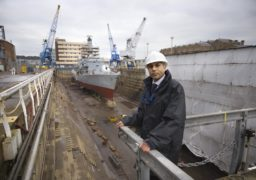 Satnam Ner, NEC member, in front of a Type 22 Royal Navy frigate being refitted in dry dock at Rosyth